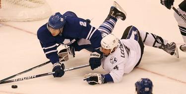 Luke Schenn and Vincent Lecavalier hit the ice hard. (Toronto Sun/Craig Robertson)