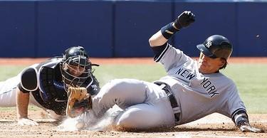 New York Yankees' Hideki Matsui slides in to score past Toronto Blue Jays catcher Rod Barajas during third-inning baseball game action in Toronto on Sept. 6, 2009. (ALEX UROSEVIC, Sun Media)