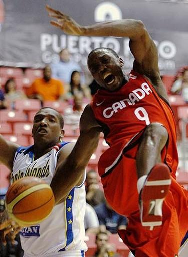 Olu Famutini (9) of Canada is blocked by Virgin Island's Freeman Reginald (L) during their men's FIBA Americas Championship qualifying round basketball game in San Juan on Aug. 28, 2009. (REUTERS)