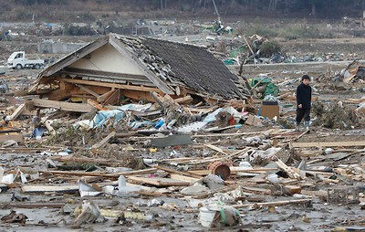 A boy walks through the rubble in Rikuzentakata, northern Japan after the magnitude 8.9 earthquake and tsunami struck the area, March 14, 2011.   REUTERS/Toru Hanai