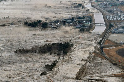 A massive tsunami hits the coastal areas of Iwanuma, Miyagi Prefecture, northeastern Japan March 11, 2011. REUTERS/KYODO
