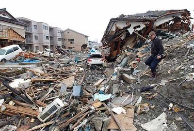 A man looks around devastated area hit by earthquake and tsunami in Kesennuma, Miyagi Prefecture in northern Japan, March 15, 2011.   REUTERS/Kim Kyung-Hoon
