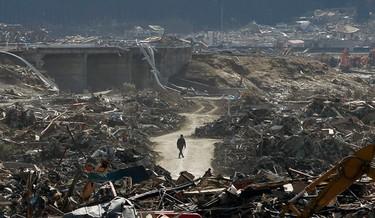 A survivor walks through debris in Rikuzentakata, Iwate prefecture, where the earthquake and tsunami hit last week, March 18, 2011. REUTERS/Aly Song