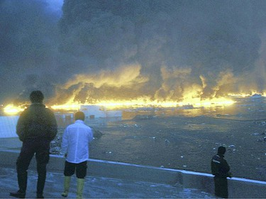 Oil floating on water burns as a tsunami hits Kesennuma city in Miyagi prefecture March 11, 2011.  (Reuters)