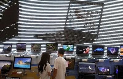 Visitors look at laptops displayed at the Microsoft booth during the Computex 2011 computer fair at the TWTC Nangang exhibition hall in Taipei May 31, 2011.  (REUTERS/Pichi Chuang)