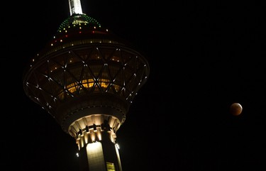 The eclipse of the moon is seen behind the Milad tower in Tehran on June 16, 2011. (REUTERS/Raheb Homavandi)