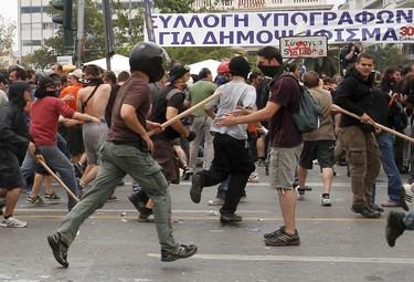 Baton-wielding demonstrators run near the Greek parliament in Athens, June 15, 2011. REUTERS/John Kolesidis