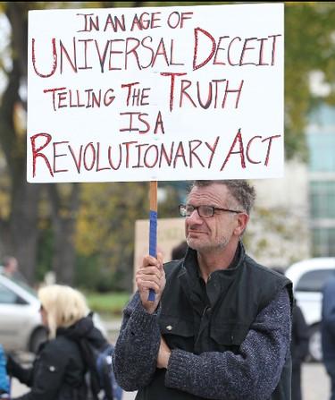 A protester waves a placard during the Occupy Winnipeg demonstration outside the Manitoba Legislative building in Winnipeg Saturday October 15, 2011. BRIAN DONOGH/WINNIPEG SUN/QMI AGENCY
