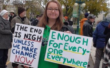 Katie Saunders holds up protest signs at the Occupy Winnipeg rally Saturday morning. (Jillian Austin/Winnipeg Sun)