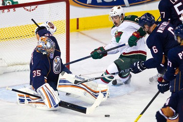 Edmonton's Nikolai Khabibulin keeps Minnesota's Cal Clutterbuck from scoring during the Edmonton Oilers NHL hockey game against the Minnesota Wild at Rexall Place in Edmonton on Friday, October 20, 2011. CODIE MCLACHLAN/EDMONTON SUN QMI AGENCY ***NOT FOR RESALE***