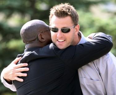 Former Bomber coach Don Burrell, hugs Doug Brown following the funeral for Bombers assistant coach Richard Harris in Winnipeg Sunday August 07, 2011. BRIAN DONOGH/WINNIPEG SUN/QMI AGENCY