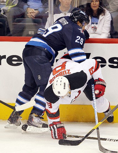 Winnipeg Jets defenceman Johnny Oduya (l) takes out New Jersey Devils Dainius Zubrus during NHL hockey in Winnipeg Saturday, December 03, 2011. BRIAN DONOGH/WINNIPEG SUN/QMI AGENCY