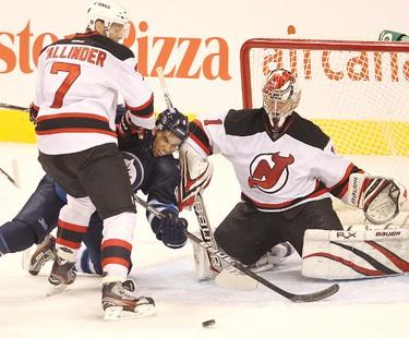 New Jersey Devils defenceman Henrik Tallinder (l) dumps Winnipeg Jets left winger Evander Kane (c) in front of Devils goalie Johan Hedberg during NHL hockey in Winnipeg Saturday, December 03, 2011. BRIAN DONOGH/WINNIPEG SUN/QMI AGENCY