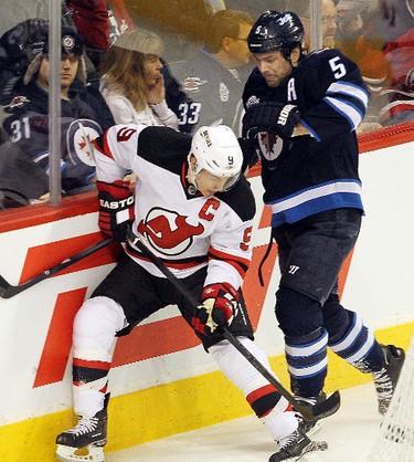 New Jersey Devils left winger Zach Parise (l) and Winnipeg Jets defenceman Mark Stuart fight for the puck during NHL hockey in Winnipeg Saturday, December 03, 2011. BRIAN DONOGH/WINNIPEG SUN/QMI AGENCY