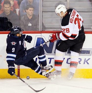 Winnipeg Jets left winger Evander Kane (l) is dumped by New Jersey Devils defenceman Anton Volchenkov during NHL hockey in Winnipeg Saturday, December 03, 2011. BRIAN DONOGH/WINNIPEG SUN/QMI AGENCY