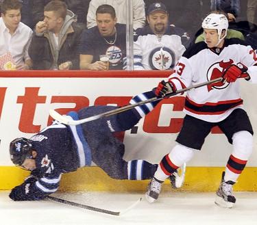 Winnipeg Jets left winger Jason Jaffray (l) is dumped by New Jersey Devils right winger David Clarkson during NHL hockey in Winnipeg Saturday, December 03, 2011. BRIAN DONOGH/WINNIPEG SUN/QMI AGENCY