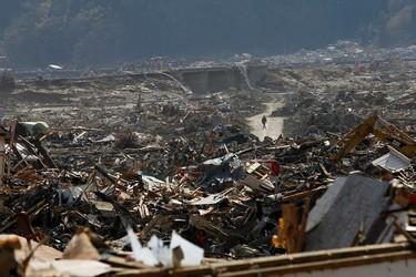 A survivor walks through debris in Rikuzentakata, Iwate prefecture, March 18, 2011, following the devastating earthquake and tsunami.   REUTERS/Aly Song