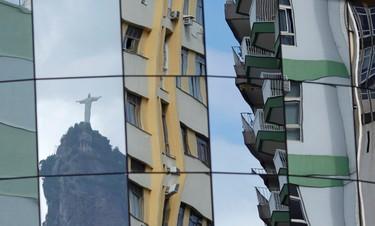 "Rio de Janeiro's ""Christ the Redeemer"" statue is reflected on the glass facade of a building in Botafogo in Rio de Janeiro February 25, 2011.  REUTERS/Ricardo Moraes"