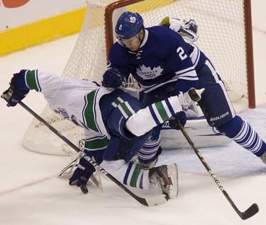 Leaf Luke Schenn (2) drops Canuck Jannik Hansen during the second period. (Jack Boland / Toronto Sun / QMI Agency)