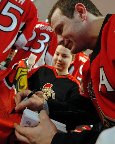 Sens_CHEO9 - December 21, 2011  - Ottawa Senators' Jason Spezza signs a flag for Lisa Laframboise during a visit to the Children's Hospital of Eastern Ontario Wednesday, December 21, 2011.  (DARREN BROWN/QMI AGENCY)