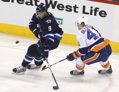 Winnipeg Jets LW Evander Kane tries to control the puck between New York Islanders defenceman Mike Mottau (left) and New York Islanders LW David Ullstrom during National Hockey League action at the MTS Centre on Tues., Dec. 20, 2011. JASON HALSTEAD/WINNIPEG SUN QMI AGENCY