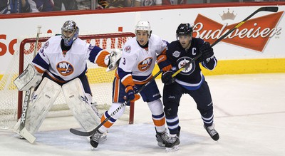 New York Islanders defenceman Travis Hamonic battles Winnipeg Jets LW Andrew Ladd in front of New York Islanders goaltender Al Montoya during NHL action at MTS Centre on Dec. 20, 2011. (JASON HALSTEAD/WINNIPEG SUN FILES)