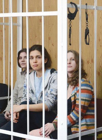 Members of female punk band Pussy Riot Nadezhda Tolokonnikova (C), Maria Alyokhina (R) and Yekaterina Samutsevich (L), sit behind the bars during a court hearing in Moscow on July 20, 2012. (AFP PHOTO/NATALIA KOLESNIKOVA)