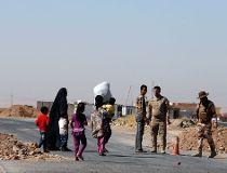 Peshmerga fighters stand guard