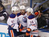 Edmonton Oilers' Ryan Nugent-Hopkins (L) and Taylor Hall (C) celebrate Jordan Eberle's
