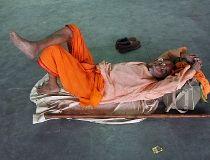 A Sadhu or a Hindu holyman sleeps at a railway station on a hot summer day in Allahabad