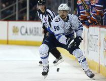 Manitoba Moose forward Austen Brassard dumps the puck into the Bakersfield Condors zone during AHL action in Winnipeg on Fri., Nov. 20, 2015. Kevin King/Winnipeg Sun/Postmedia Network