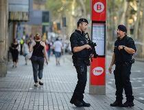 Armed police officers patrol a street in Las Rambla